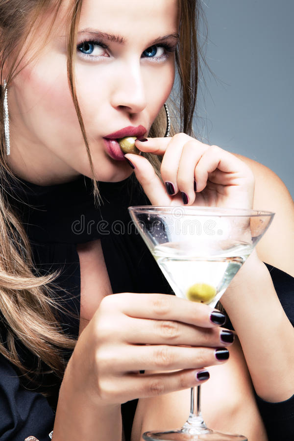 Woman with glass of martini. Young woman with glass of martini and olive in mouth, studio shot stock images
