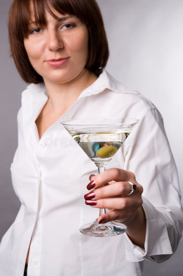 The woman with a glass of martini. The woman in a white shirt with a glass of martini royalty free stock photo
