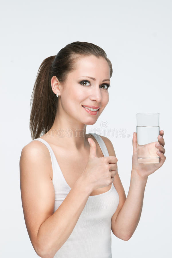 Woman with glass of water. Attractive caucasian smiling woman isolated on white studio shot drinking water with thumb-up royalty free stock image