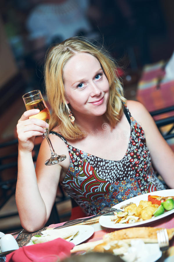 Woman with glass of wine in restaurant royalty free stock images