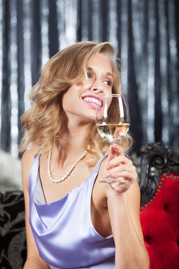 Woman with glass of wine. Smiling woman with glass of white wine having fun in the restaurant royalty free stock images