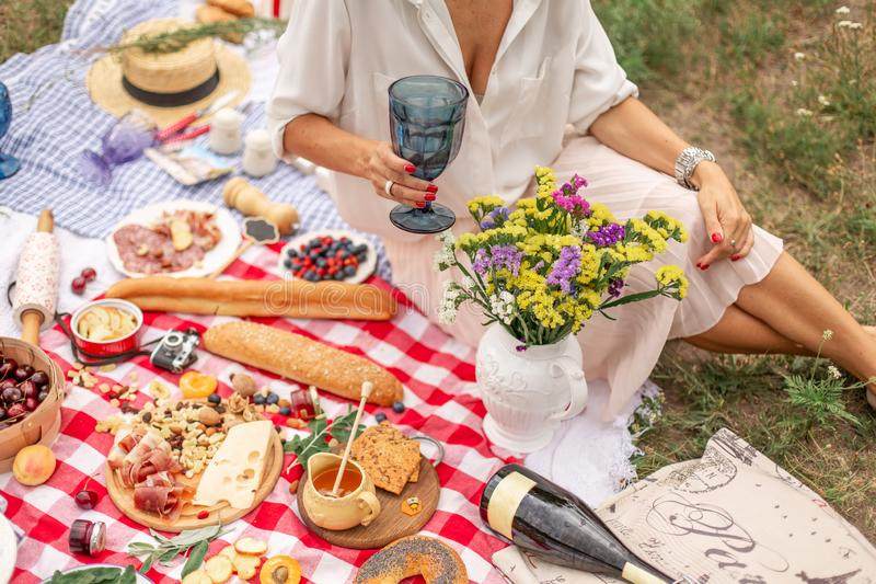 Woman with glass of wine sit on chekered picnic blanket. Romantic outdoor picninc on green lawn royalty free stock photo