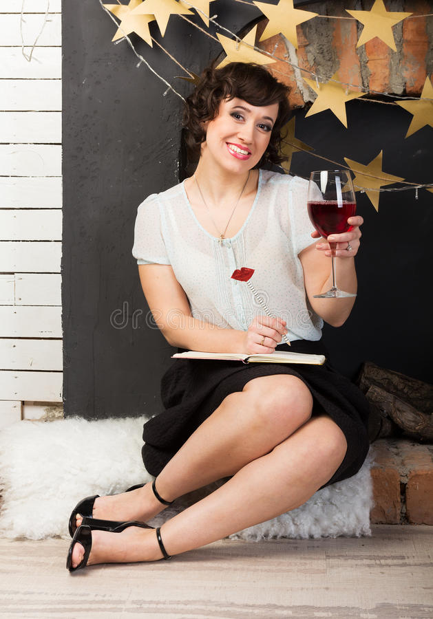 Woman with a glass of wine. Woman writing her journal with a glass of red wine royalty free stock photo
