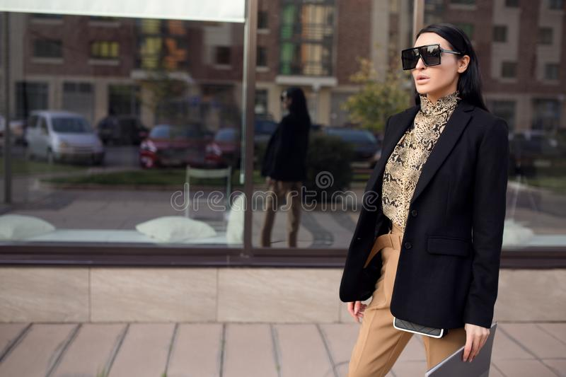 Woman in glasses and a business suit holds a folder in her hands. Leopard print stock image
