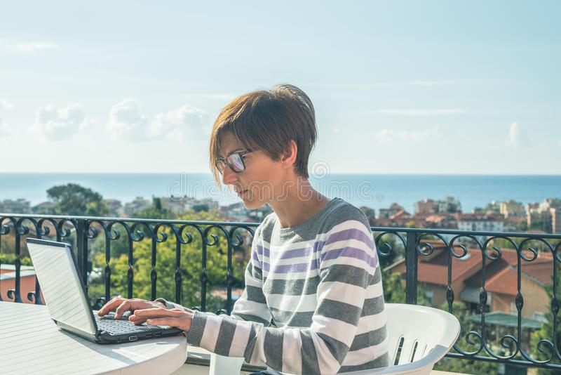Woman with glasses and casual clothings working at laptop outdoors on terrace. Beautiful background of green hills and blue sky in royalty free stock images