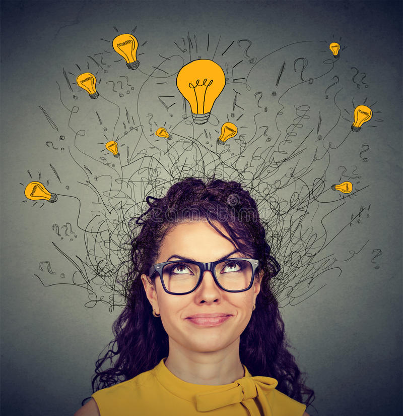 Woman in glasses with ideas light bulbs above head looking up. Young woman in glasses with many ideas light bulbs above head looking up on gray wall background royalty free stock photos