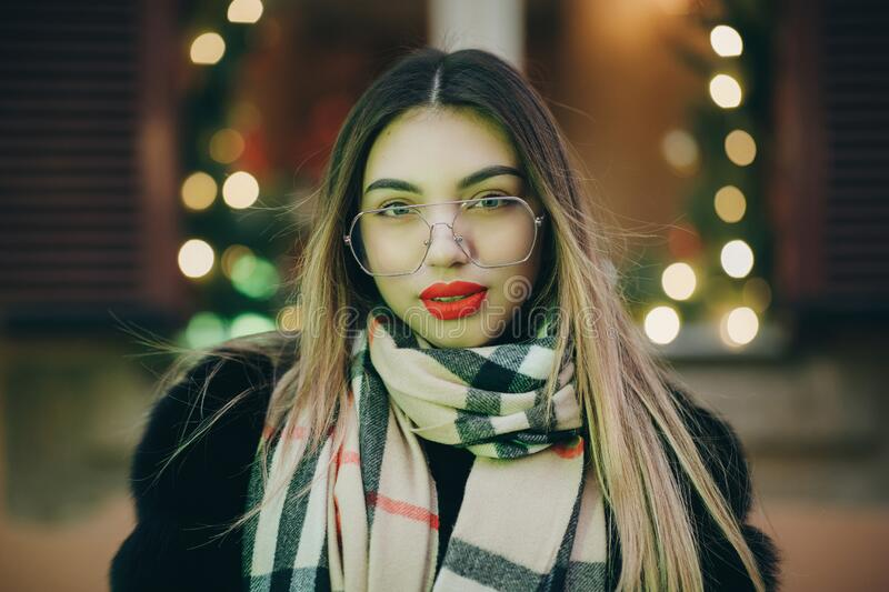 Woman with glasses look at camera poses in city center Beautiful hair attractive smile girl. Close up shot Woman with stock photography
