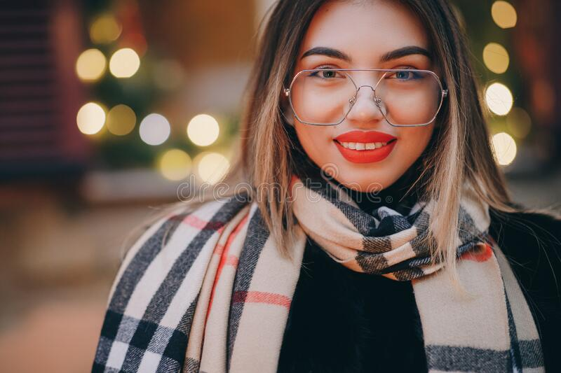 Woman with glasses look at camera poses in city center Beautiful hair attractive smile girl. Close up shot Woman with royalty free stock images