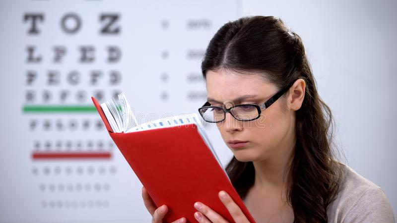 Woman in glasses suffering myopia reading book, need in correct lens diopter. Stock photo stock photography