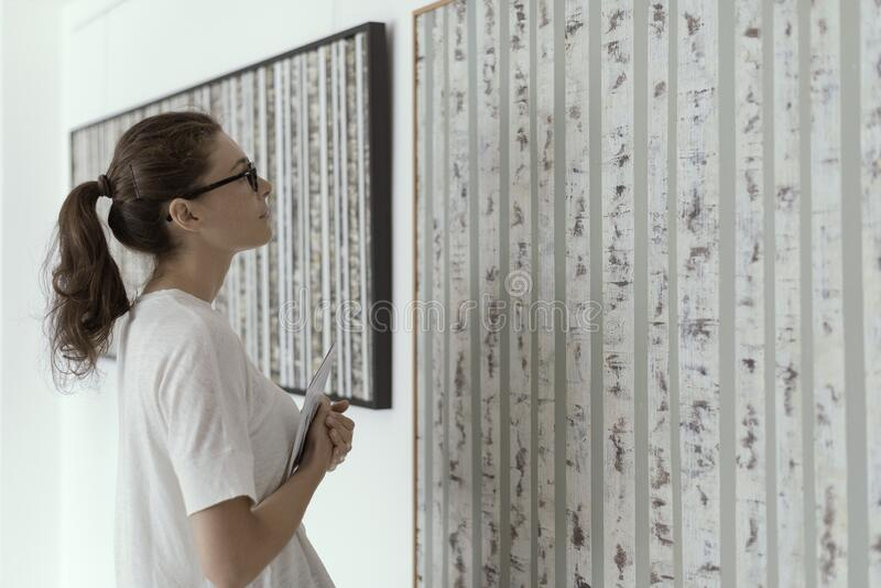Woman standing in the art gallery and looking at the paintings stock photo