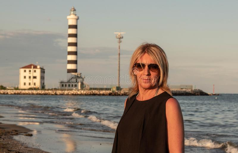 Woman with glasses who is photographed on the beach with a lighthouse behind her for navigators. photo taken on the beaches betwe. En Jesolo and Cavallino royalty free stock photo