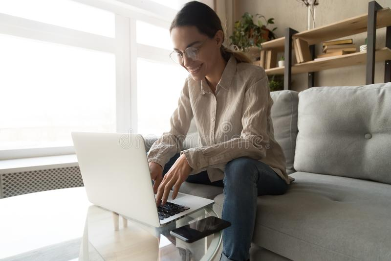 Woman in glasses working typing on computer feels satisfied. View from bottom to top attractive woman in glasses sitting on couch in living room freelancer stock photos