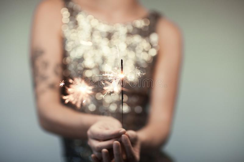 Woman in glitter dress holding sparkler, close up hands, romantic look stock photography