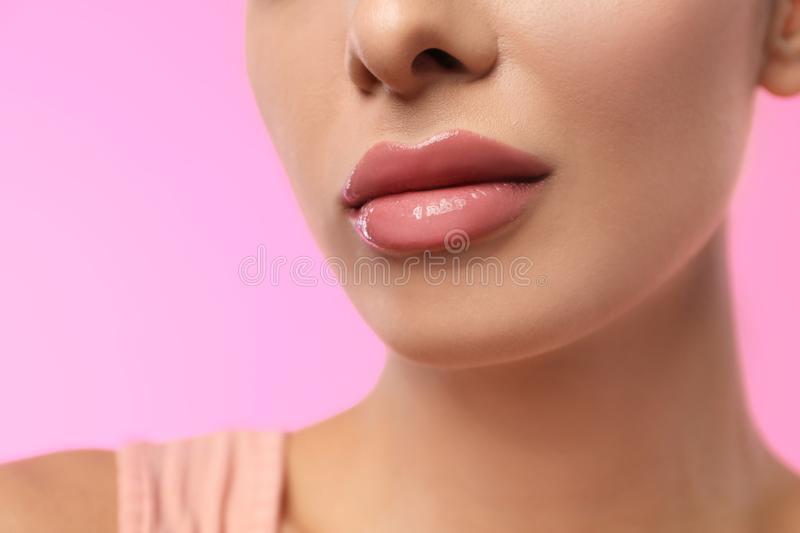 Woman with glossy lipstick on pink background royalty free stock images