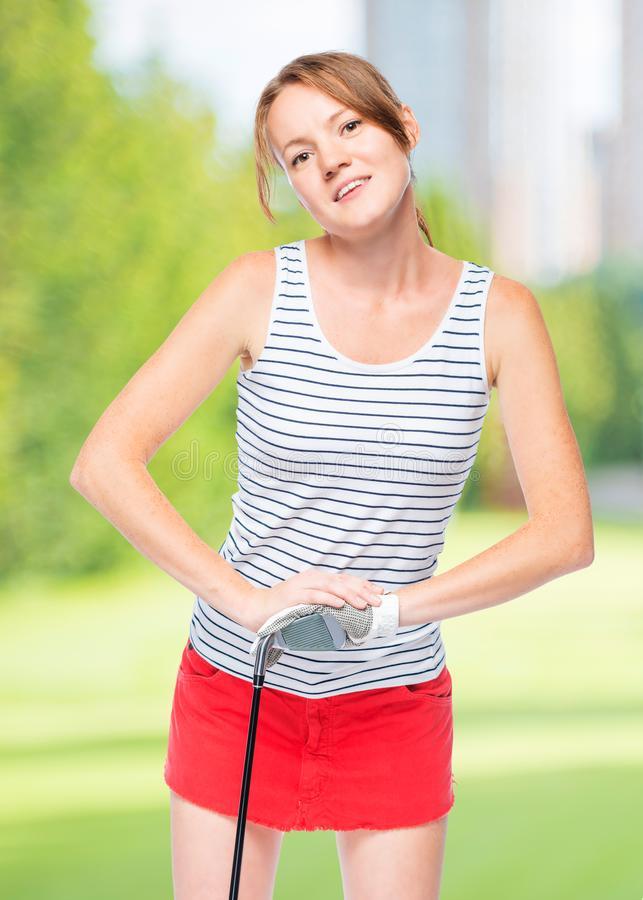 Woman in glove for game leans on golf club royalty free stock photography
