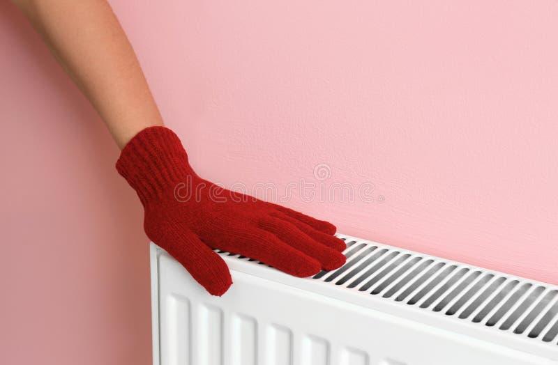 Woman in glove warming hand on heating radiator royalty free stock photos