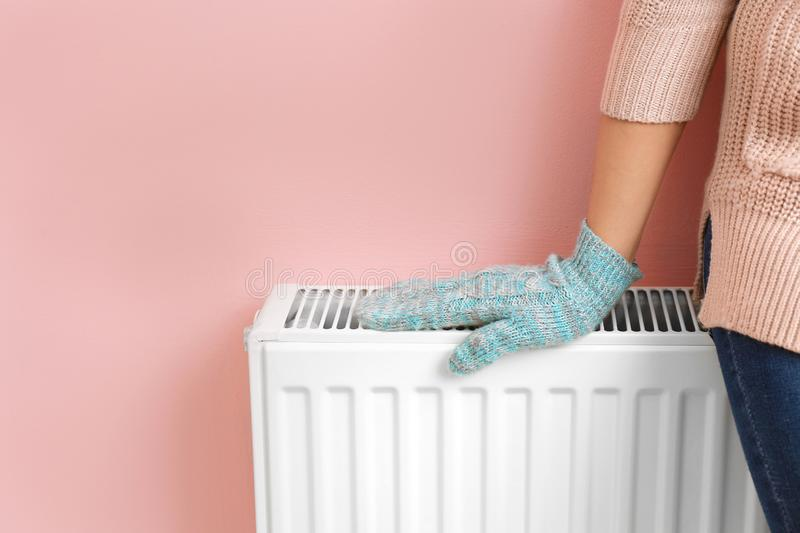 Woman in glove warming hand on heating radiator near color wall royalty free stock image