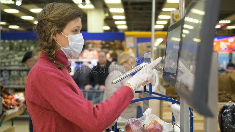 Woman in gloves and mask weighs apples touch screen electronic scales in supermarket, coronavirus in public place. Young beautiful girl in plastic gloves and royalty free stock image