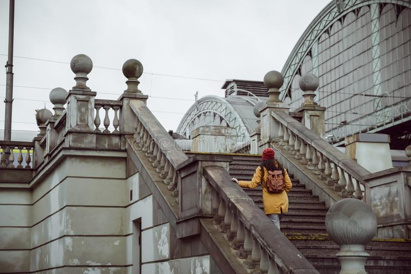 Woman go up by stairs to railway station. Dramatic rainy weather outside royalty free stock images