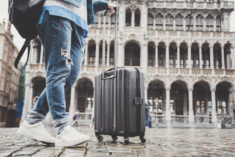 Woman tourist goes with a suitcase at the Grand Place in Brussels, Belgium royalty free stock photo