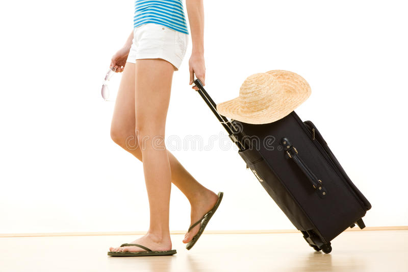 Woman going on holiday. Side view of female holidaymaker in flip flops pulling suitcase with sun hat on top, white background stock photography