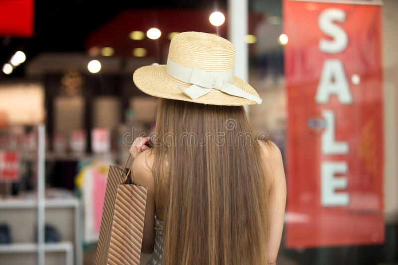 Woman going for shopping on sale time. Young pretty stylish long-haired woman wearing hat in shopping mall, walking in clothes store, holding brown shopping bag royalty free stock images