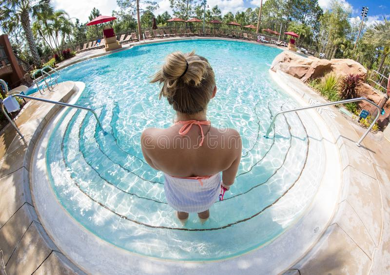 Woman going swimming in a large outdoor resort pool. View from behind of a woman entering in a luxurious outdoor swimming pool at a beautiful resort. Unique wide stock photography
