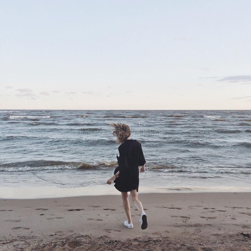 Woman Going Toward the Sea Under Clear Skies stock photos