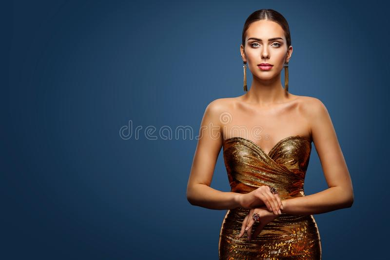 Woman Gold Dress, Fashion Model Sparkling Sequin Gown, Young Girl Beauty Portrait. Over studio Blue Background royalty free stock photos