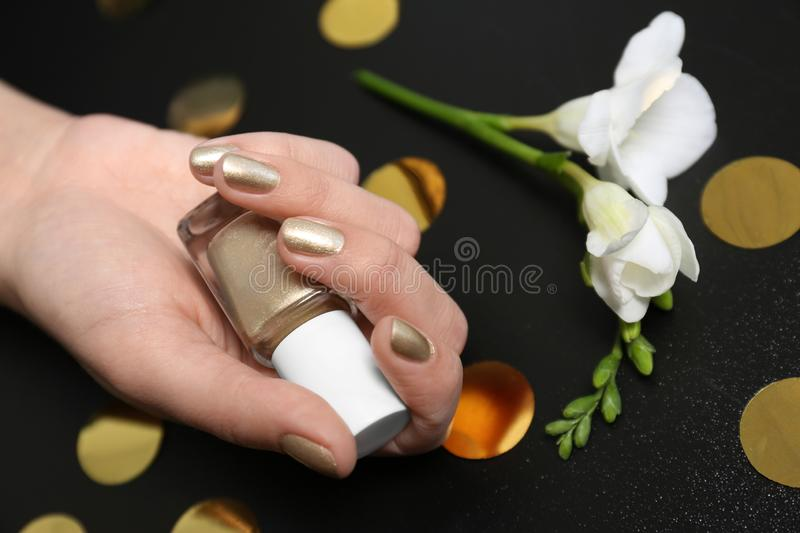 Woman with golden manicure holding nail polish bottle on black background. Closeup royalty free stock images