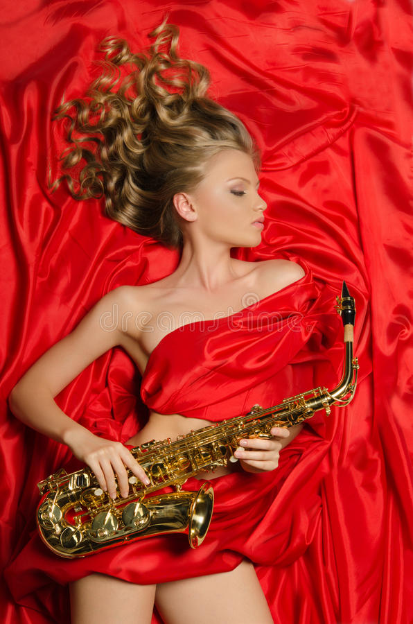 Woman with golden saxophone lying on red silk royalty free stock photos