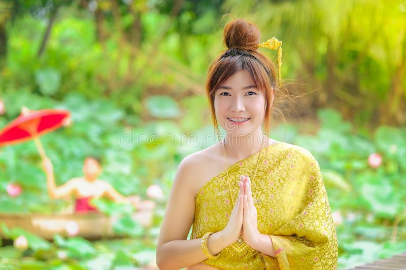 Woman in the golden Thai dress is good morning in the lotus garden. The women in the golden Thai dress is good morning in the lotus garden stock images