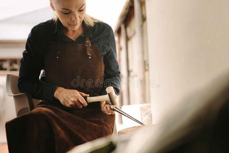 Woman goldsmith making a jewelry at workshop stock images