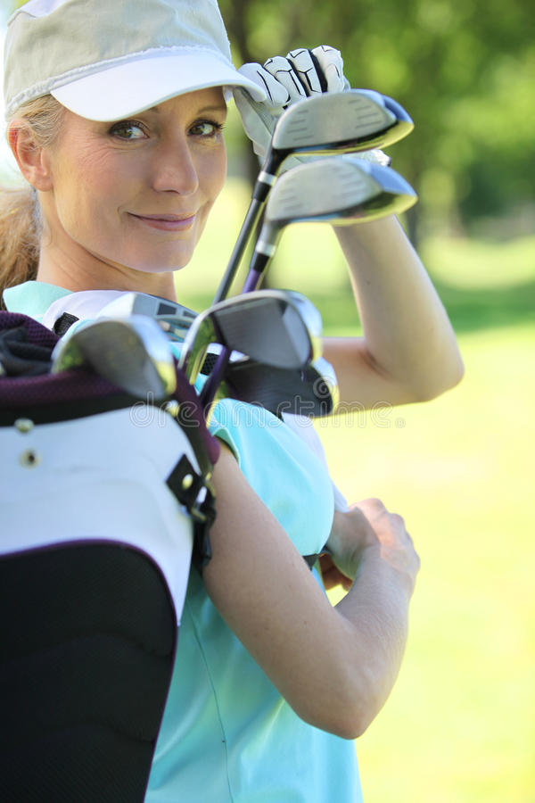 Woman with golf clubs. Woman carrying her golf clubs stock photos