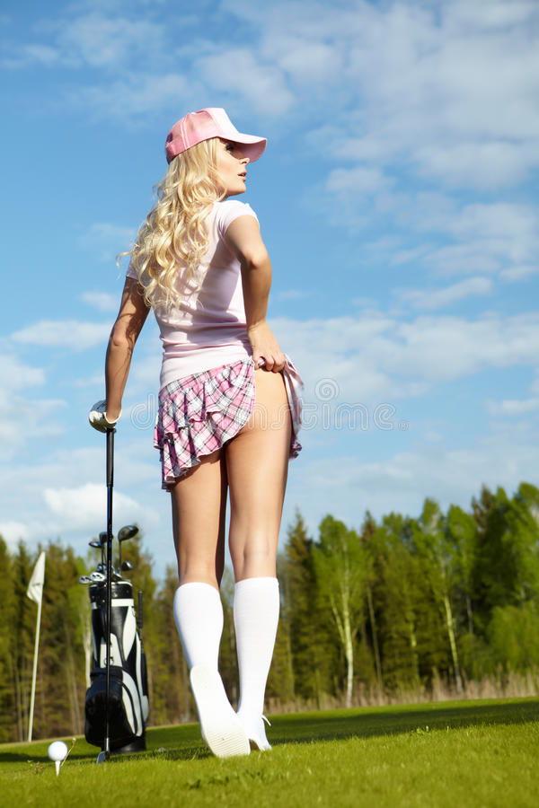 Woman with golf equipment. Young blonde woman with golf equipment stock image