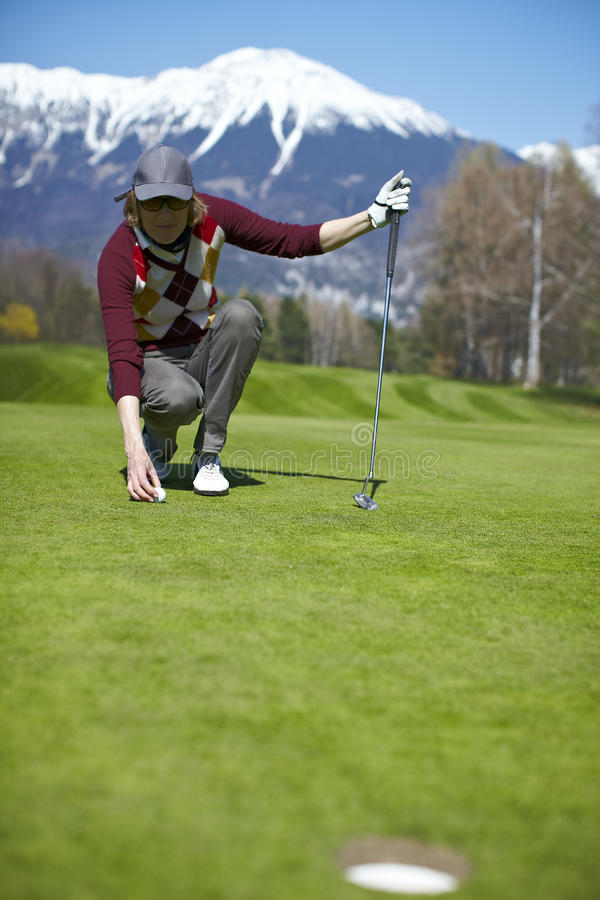 Woman Golfer Aligning Golf Ball Royalty Free Stock Image