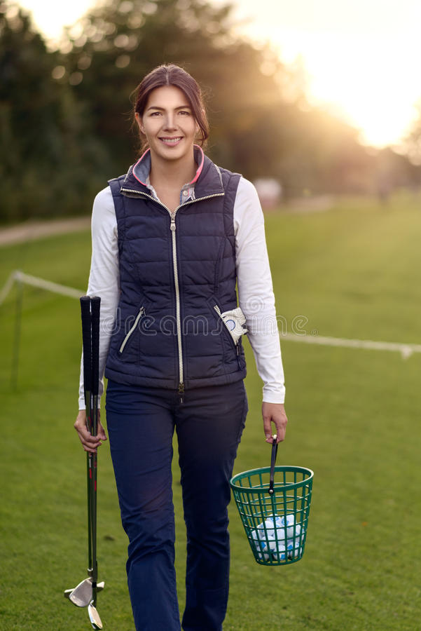 Woman golfer carrying balls on a driving range stock images