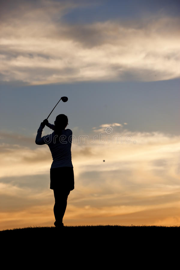 Woman golfer hits ball. royalty free stock photography