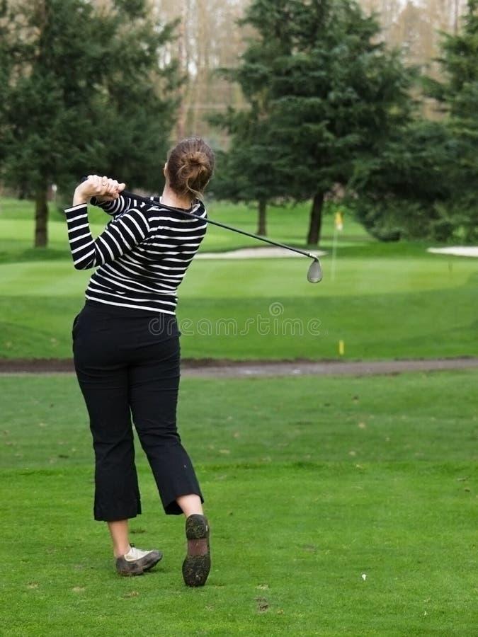 Woman golfer swing stock photography