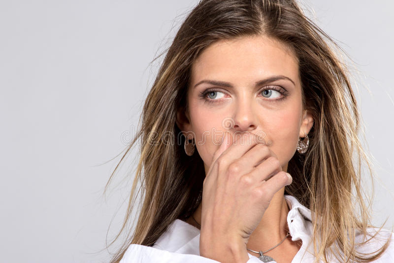 The woman with good skin closing a mouth a hand. On grey background royalty free stock photos