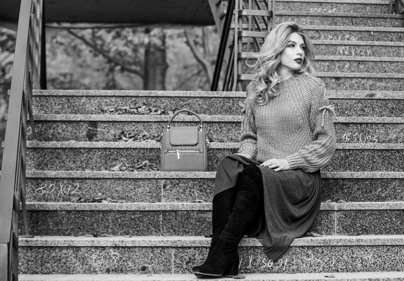 Woman with gorgeous hairstyle sit on stairs outdoors. Fall fashion trend. Layer oversize knit over girly skirt. Wearable. Trends. Fall outfit formula. How to stock image