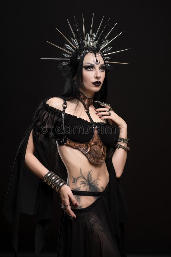 Woman in gothic suit and silver crown stock images