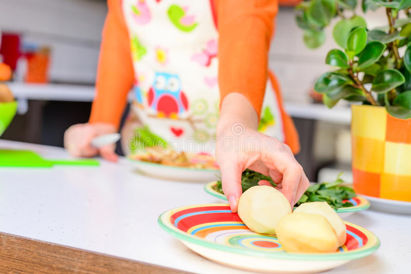 Woman grab peeled potato by hand,in modern kitchen royalty free stock photography
