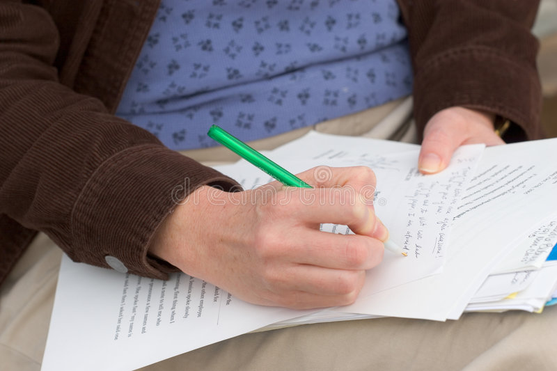 Woman Grading Papers. Photo of a woman grading papers stock photo