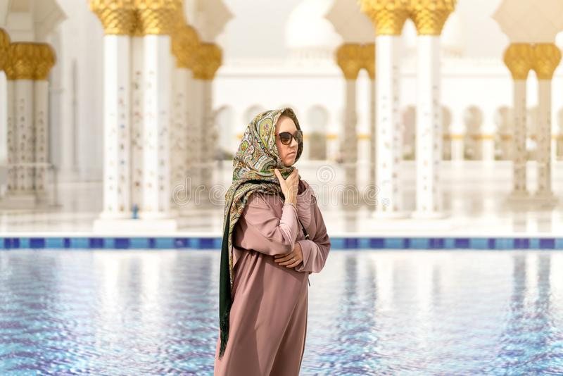 Woman in grand mosque of Sheikh Zayed in front of water. Islamic decor. Female tourist in muslim country. royalty free stock photos