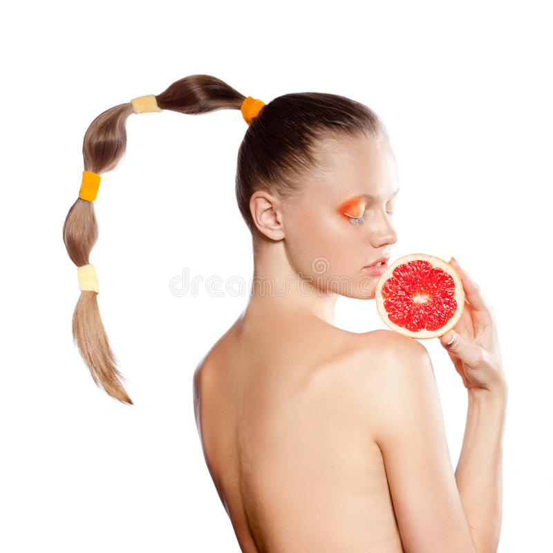 Woman with grapefruit and creative hairstyle. Beautiful woman with grapefruit and creative hairstyle over white stock photo