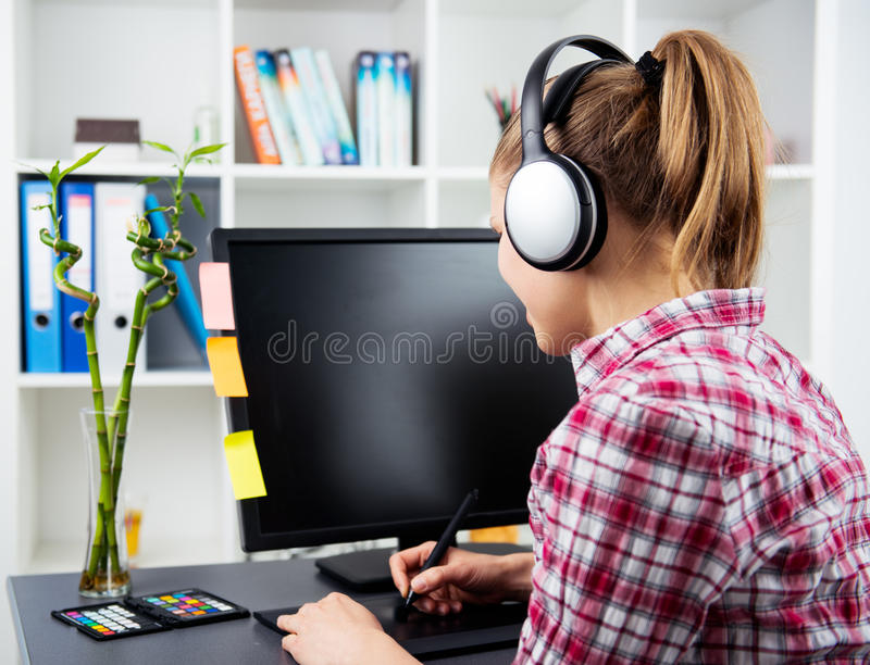 Woman graphic designer in headset. House interior design. Smiling girl in headset working with color samples. Creativity and professionalism stock images