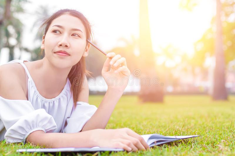 The women is on the grass and beautiful. She is thinking. the book is on the grass. she wear white dress. stock photo