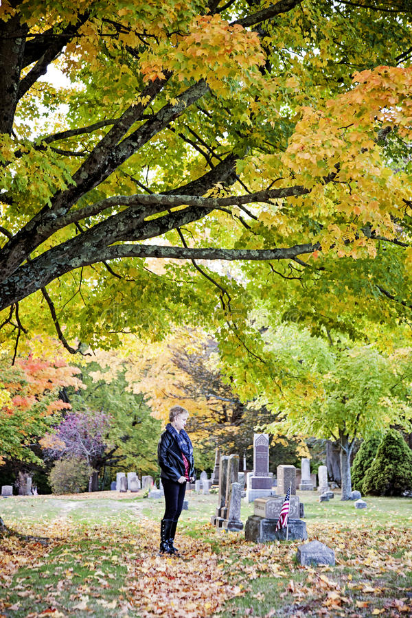 Woman at grave in cemetery. A side view of an elderly woman standing at a headstone in a cemetery in Autumn royalty free stock photography