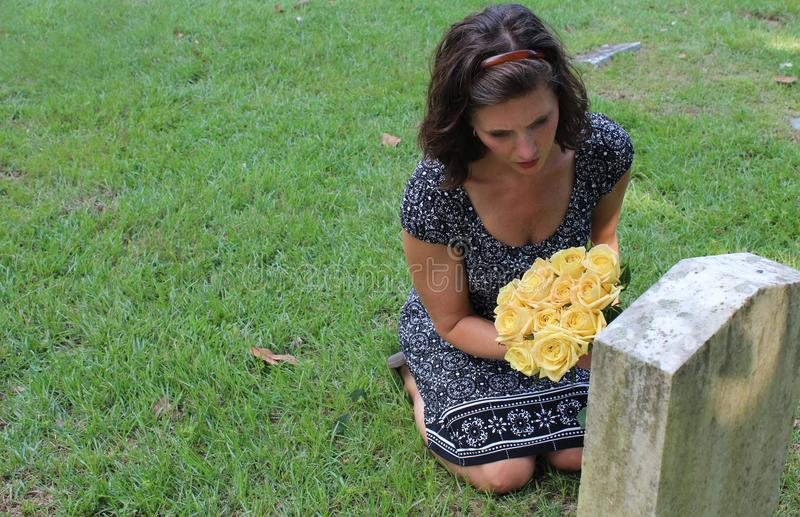Woman at grave stone with yellow flowers. royalty free stock photos